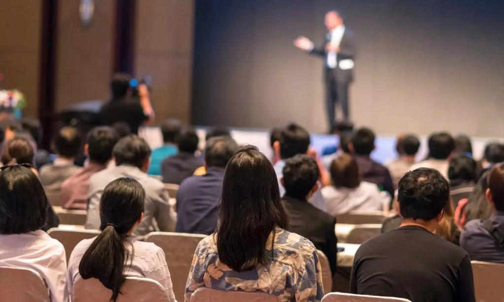 multidão de pessoas em um auditório sentadas em um evento de comércio exterior