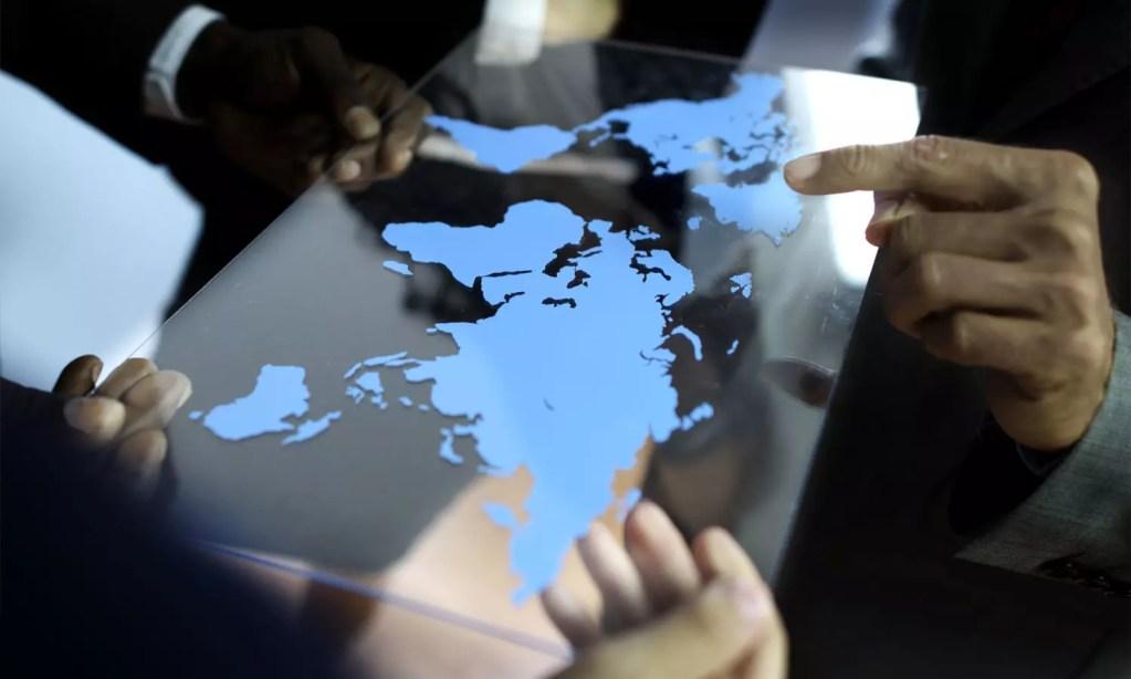 vários executivos segurando um mapa e apontando destinos de investimento em exportação