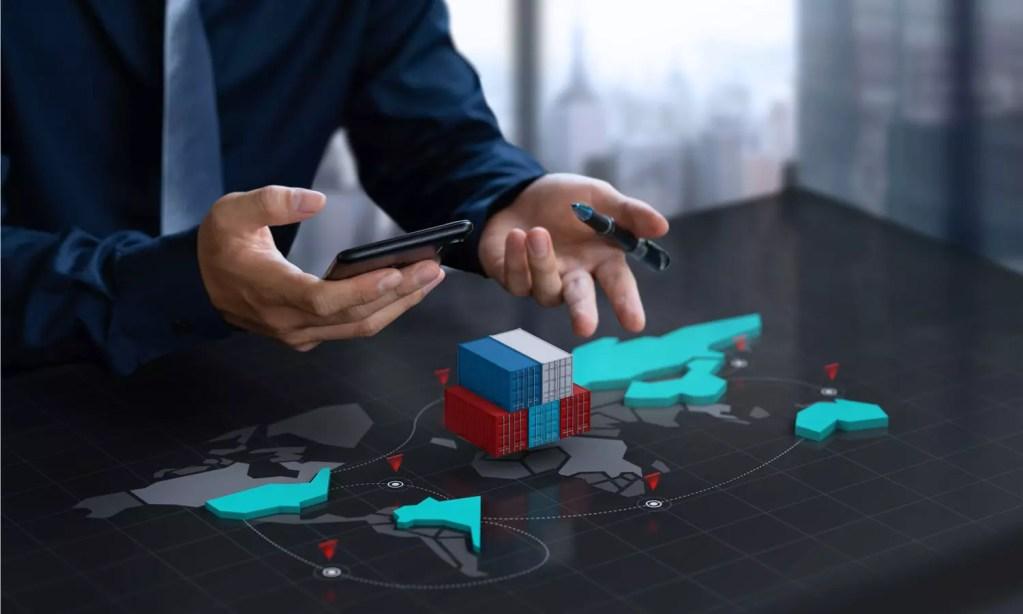 executivo com o smartphone na mão analisando no mapa o processo de frete internacional